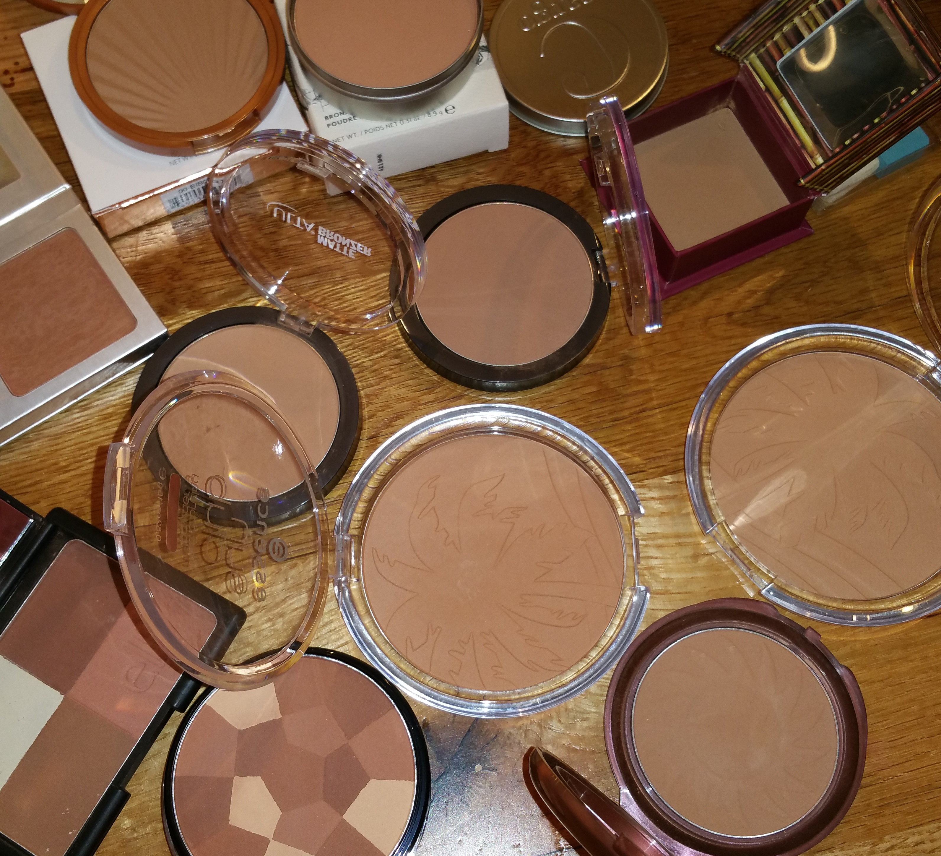 Starting from bottom left: e.l.f. Cool Bronzer, NYC Color Wheel - All Over Bronze, and Smooth Skin Bronzing Face Powder; Second row right to left: Essence Sun Club - 01 Natural and 02 Sunny; Third row: left to right: Ulta Matte Bronzer Warm and Cool; Top row right to left: Benefit Hoola, Cargo Matte Bronzer - Medium, Laura Geller Matte - Medium, and It Cosmetics CC + Bronzer.