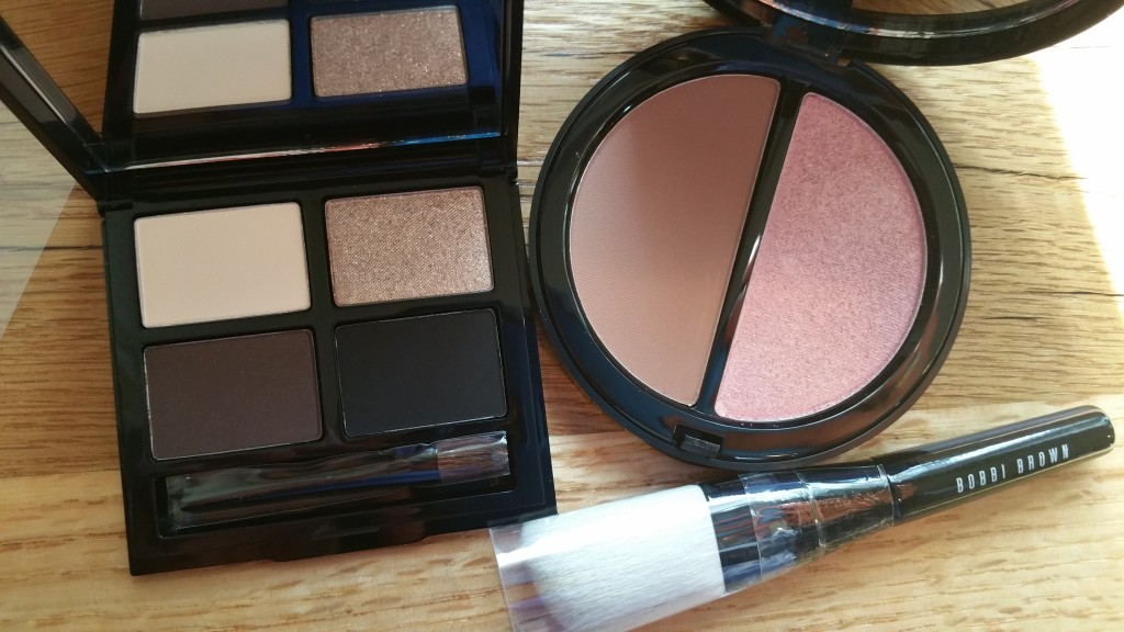 Bobbi Brown Cosmetics Define and Glow Set: Eyeshadow Palette, Bronzer/Highlighter compact, and mini Angled Face Brush.